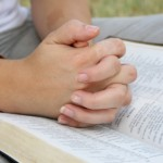 hands-folded-on-bible